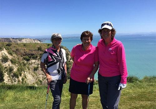 Golfers posing for a picture on the golf course overlooking the ocean